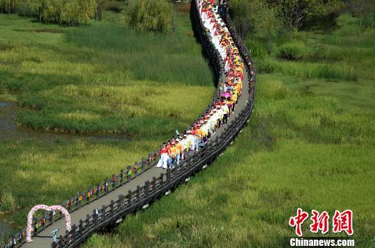 """66对""""新人""""牵手走过走婚桥。刘忠俊摄"""